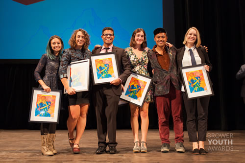 photo of young people on a stage, holding awards