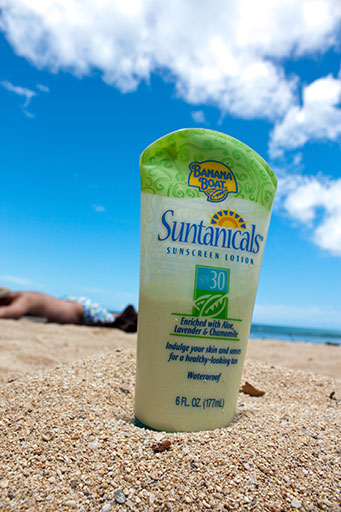 photo of sunscreen on a sandy beach