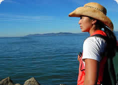 photo of a young woman in an orange vest looking thoughtfully at the Bay