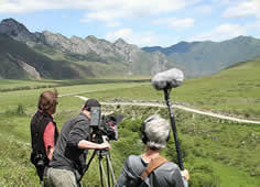 photo of people filming in a green mountain setting