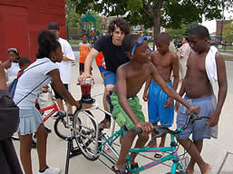 photo of a young man and some kids on a stationary bike attached to a blender - they are having fun
