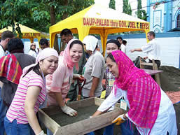 photo women working a large sifter. they are wearing colorful head scarves and smiling