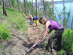 photo of people building a trail on the shore of a large blue lake